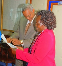 Assistant Minister, MEMR, Hon. Prof. Kamar and the PS, Mr. Ali Mohamed perusing thro' the title deed of the ten acres  before presenting it to the RCM.