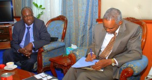 PS, MEMR, Mr. Ali Mohamed signing the letter to officially forward the ten acres of land to the Regional Centre for Mapping. Looking on is the DRSRS Director, Mr. Jaspat Agatsiva.