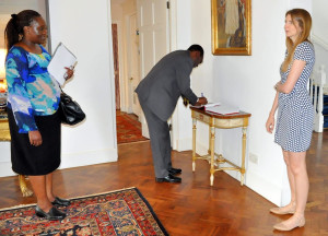 Environment PS Dr. Chris Kiptoo signs the visitors book at the British High Commissioners' residence in Muthaiga, looking on is Director Climate Change Dr. Pacifica Ogola( Left), and HC Jane Marriott.  (RIght).
