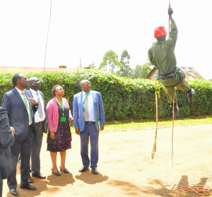 09.03.2020:- A seed harvester prepares to climb a tree to harvest seeds at KEFRI, as the PS and other officials look on.