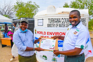 urkana County Environment Director Clement Nadio (right) hands over a certificate to Esimit Echakan for participating in the Turkana County Environment Competition.