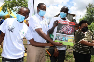 Youths from Kombo green group in Korogocho and NEMA DG Mamo B Mamo display poster to raise awareness on protection of the earth  during the Earth Day  celebrations held in Korogocho Nairobi County.
