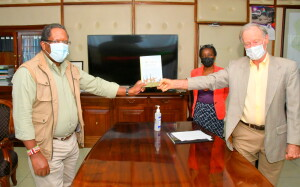 Environment & Forestry CS Keriako Tobiko receives a book entitiled we are one from Dr. David Western